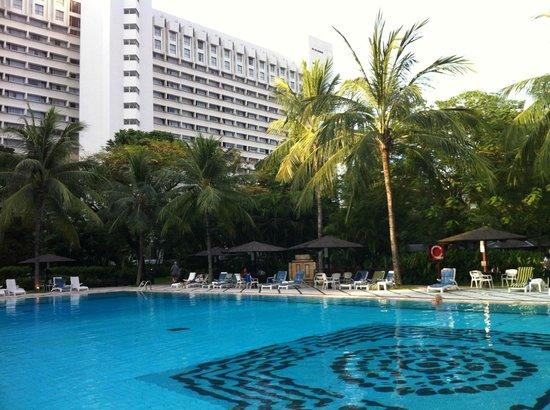 Hotel Borobudur Jakarta: L'immeuble de l'hôtel derrière le jardin luxuriant