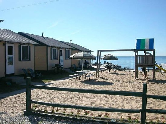 East Tawas, MI: 3 of the cabins and the sandy play area for kids!