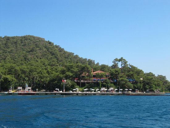 TUI Sensimar Marmaris Imperial Hotel: The hotel, from the water taxi to Marmaris. Hotel is behind trees in the centre, beach to the ri