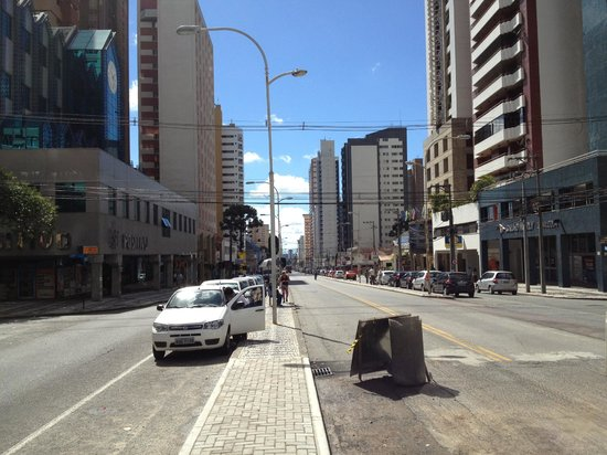 Four Points by Sheraton Curitiba: Hotel is halfway down the block on the right, with international flags above a dark facade