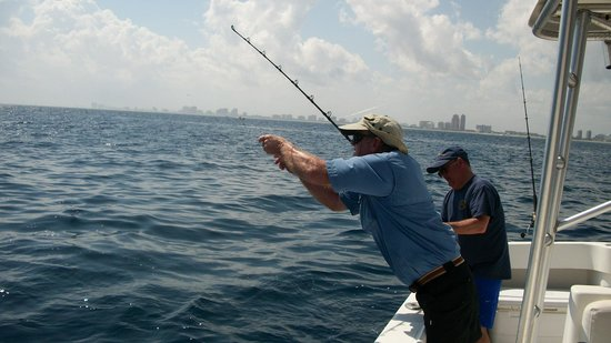 Lady Helen Fishing Charters: Capt Jeff removing weights from line to enable reeling in fish