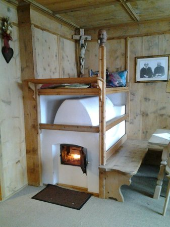 Dolomites Inn: печка с кроватью наверху
