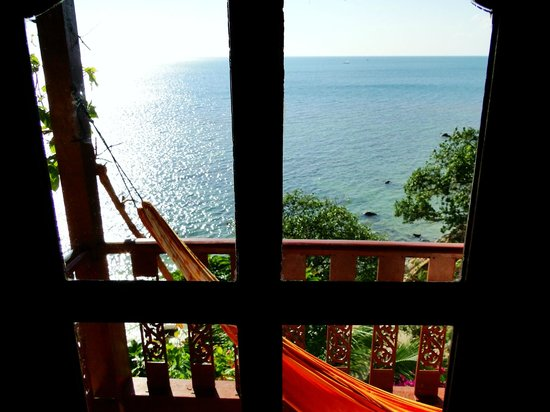 Paradise Cove Hotel: View Through Window of Villa 6 with Relaxing Hammock on Balcony for Sunset Viewing