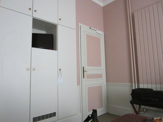 Hotel Sainte Beuve: view of door to room from bed, ample closet space, mini fridge, and TV