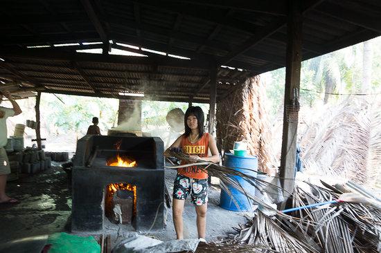 Coconut Sugar Farm: девушка, которая поддерживает огонь в печи