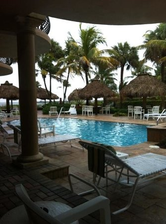 High Noon Beach Resort : pool area with tiki huts