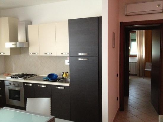 Residence Arianna: Scorcio del piano cottura e della camera da letto.