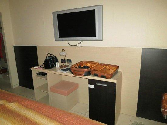 Motel Autosole 2 S.R.L: Grande televisore a parete e, sotto, l'unico arredo della camera