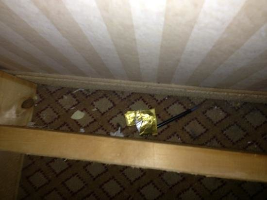 Knights Inn Madison Heights : used condom wrapper behind bed.