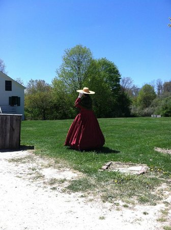 Old Bethpage Village Restoration: Holding her broad-rimmed hat from flying away
