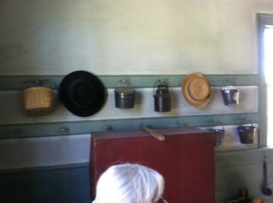 Old Bethpage Village Restoration: Hats and lunch pails hang on wall of school house