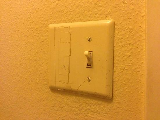 Motel 6 Alexandria - South : A missing light switch. Instead of fixing it they just taped over it and then painted the tape!