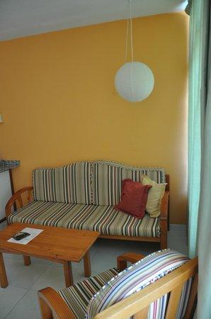 Apartamentos Las Dunas: Диван и столик в гостиной