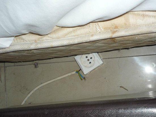 Miami Hotel: Steckdose mit unisolierten Stromkabeln. Lebensgefahr!