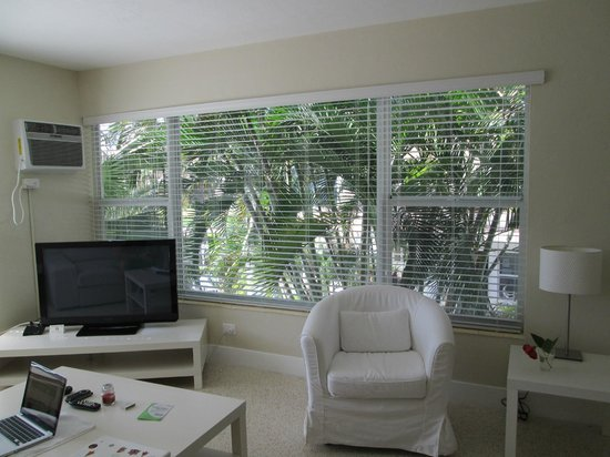 Winterset Hotel: Living room with 2 large windows overlooking the pool and tropical trees