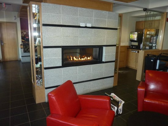 Hotel & Suites Le Dauphin Quebec: Fireplace between reception and a breakfast room