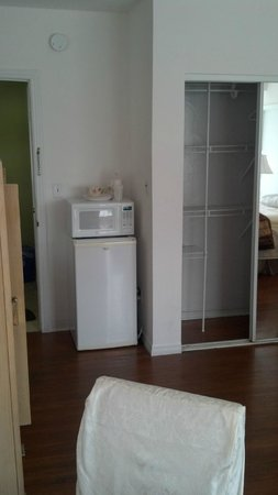 Seville Hotel & Apartments : Mini Fridge, Microwave, & Closet Near the Room Entrance Door