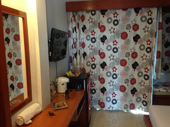 B-Bossa Patong Hotel: The TV and minibar from the doorway. The curtains are lined on the back so the room gets nice an