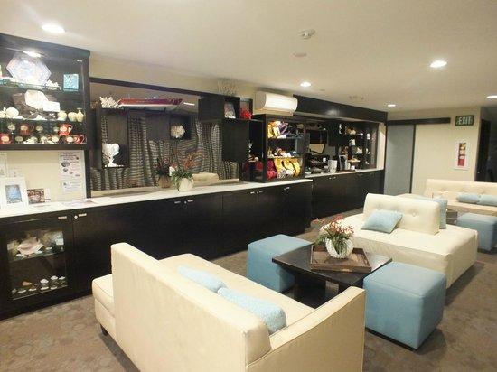 Aurora Hotel : Wonder wall of desk, books, Keurig machine and fridge