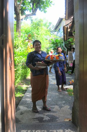 Kebun Indah: Wayan Warini coming from the reception area with flowers for the rooms