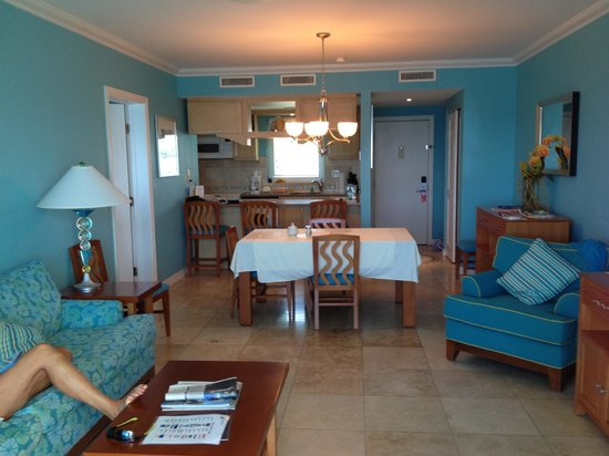 Oyster Bay Beach Resort: LIVING ROOM WITH KITCHEN IN BACKGROUND