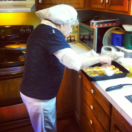 Lazy Fox Inn: Ms. Ginny buttering the homemade biscuits