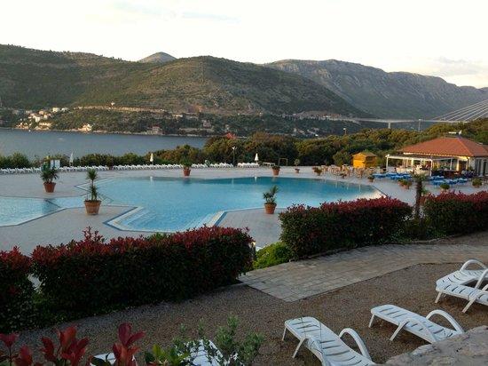 Valamar Club Dubrovnik: Piscina con la playa al fondo. A la derecha bar con atracciones por la noche