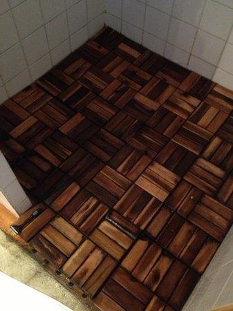 Le Prieure des Sources : sol de la douche avec dalles en bois d'une propreté douteuse et avec des champignons