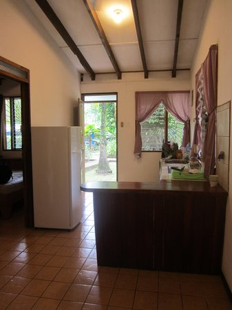 Cabinas Caribe Luna: Kitchen from the living area with (unused) television