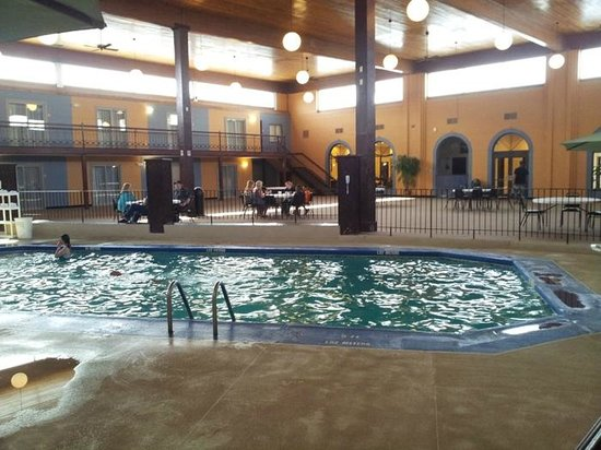 Quality Inn & Suites Coldwater: The breakfast room to the far left in the background and tables along the pool too.