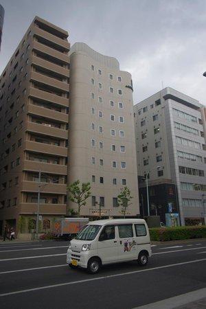 Agora Place Asakusa: Здание отеля в центре, с вогнутой стеной.