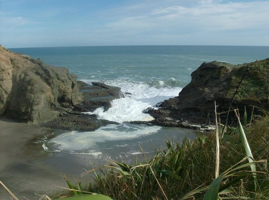 Piha Beach: The waves charging over the rocks