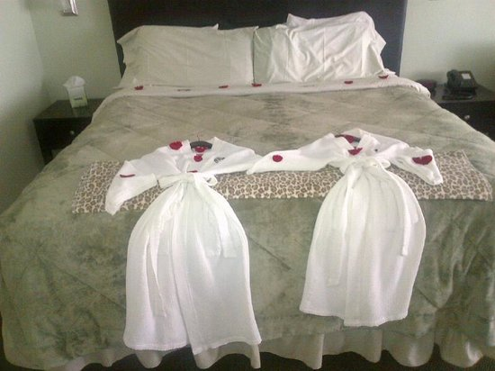 Beachfront Manor Hotel: Robes and bed with rose petals and chocolates