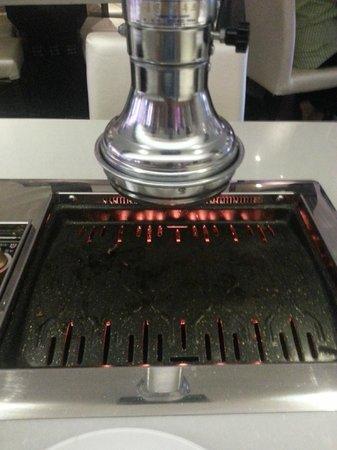 Restaurant Grillad'oc : Une table avec sa zone de cuisson et sa hotte