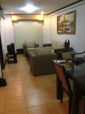D'Leonor Hotel: suite with dining table and sofa set and tv at background