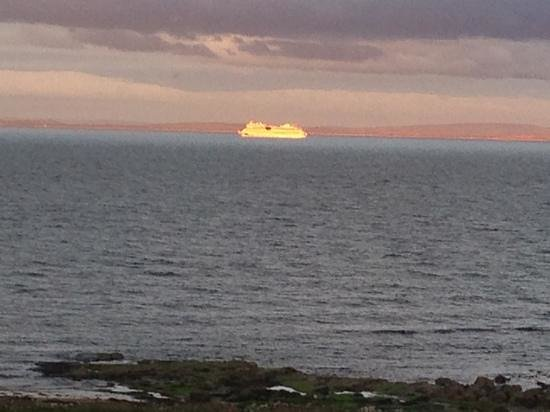 Ros-Mhor Bed and Breakfast: The sun setting causing a ship in the distance to glow, beautiful to watch