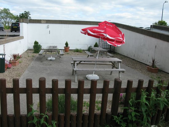 Coventry Hill Hotel: Rear seating area next to car park ramp. 1 parasol broken.