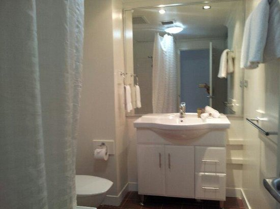 Oaks Goldsbrough Apartments: Clean Bathroom With Hair Dryer In The Cabinet  And Fluffy Towels,