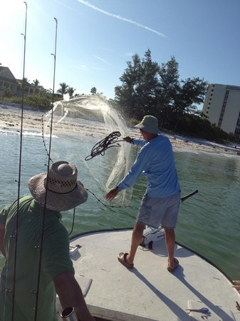 Lucky Dawg Fishing Charters: Cap'n Jack quickly casting a bait net for more live minnows