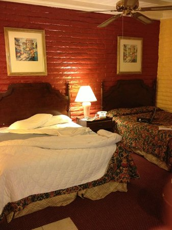 Fallbrook Country Inn: BRIGHT red and yellow walls. Red & blue comforter and torn and frayed dust ruffle
