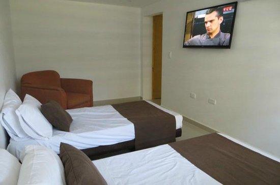 Hotel American Golf: Vista de la habitación con dos camas, tv y silla (escritorio detrás)