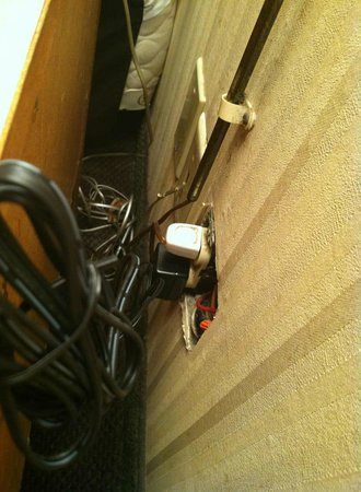 Quality Inn Dutch Inn: Electric outlet behind nightstand
