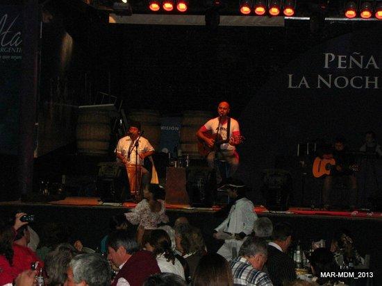 Pena's Nochera de Kike Teruel: Adentro, los juglares en el escenario y dos bailarines debajo con trajes autóctonos