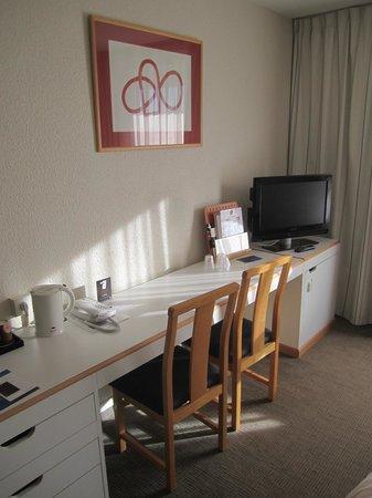 Hotel Novotel Perpignan : Einrichtung und TV im Schlafzimmer