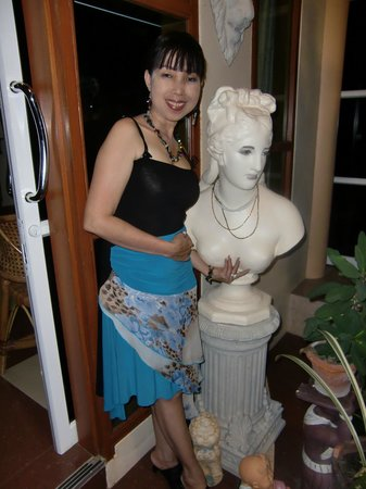 Phadaeng Mansion: Kim next to a statue in their art filled foyer