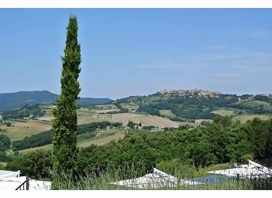 Castello di Casole Private Estate & Spa: view over the pool to casole d'elsa