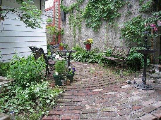 Gîte Au Beau Milieu: Courette et jardin.