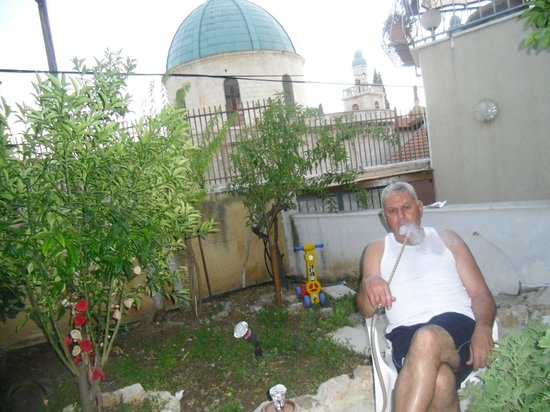 Cana Wedding Guest House: enjoy man smoking shesha in the garden next wedding church