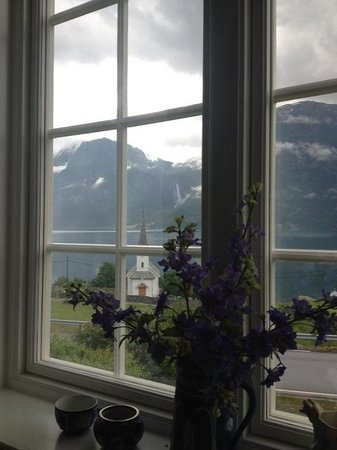Nes Gard: View from the living room onto the old stave church in Luster and the Feigenfossen waterfall