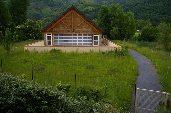 Lagrange Confort+ Residence les Pics d'Aran : Vue de la piscine, l'aire de badmington à coté est dans le même état